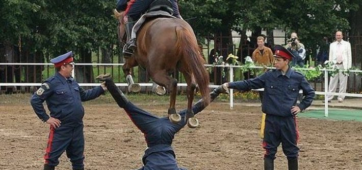 horse jumping over man's crotch