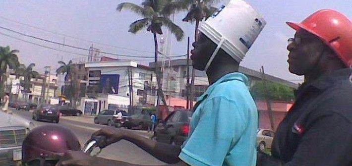 guy riding a motorcycle with a bucket on his head