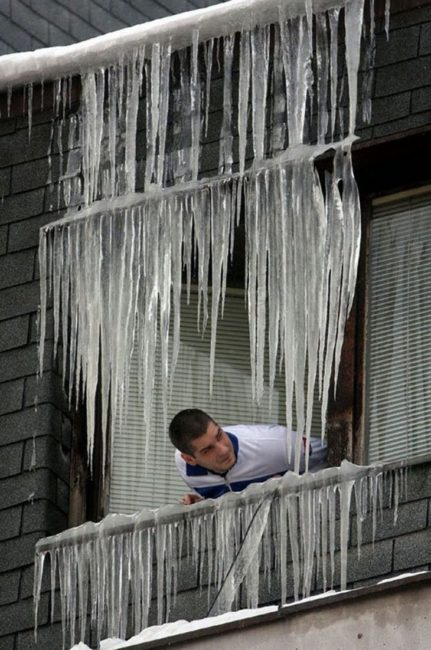 guy sticking head of window covered with icicles