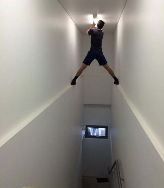 guy changing light bulb in high staircase dangerous