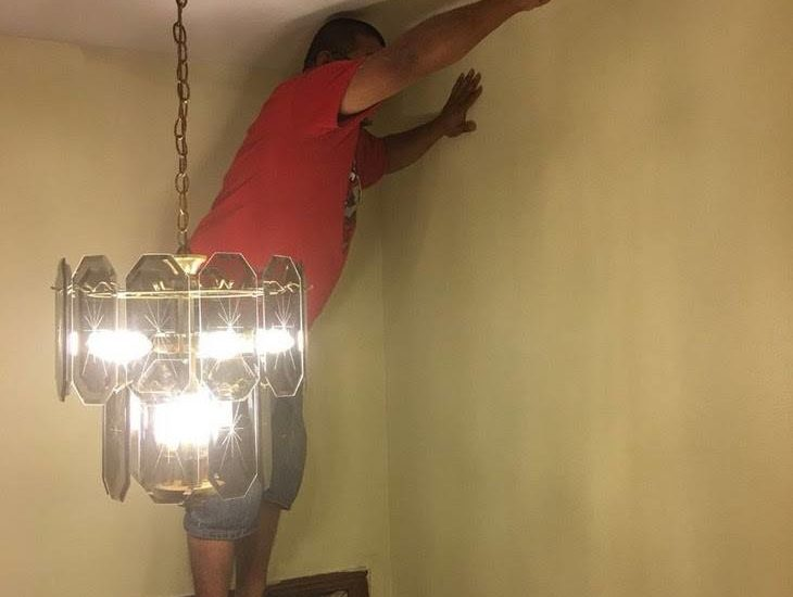 painter stands on door to paint ceiling funny