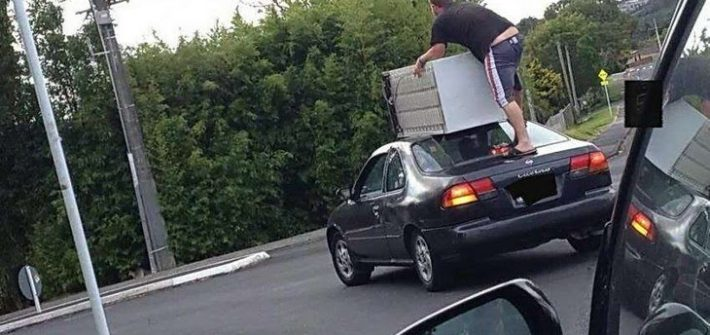 guy standing on moving car with a dresser