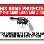 funny sign protected by the good lord and a gun